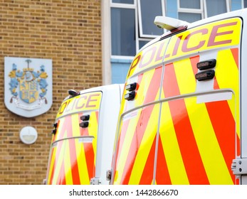 Bournemouth, Dorset/UK - June 26th 2019: The rear of two British police response vans with Police signs and chevrons in orange on yellow with a police crest on a wall blurred in the background.