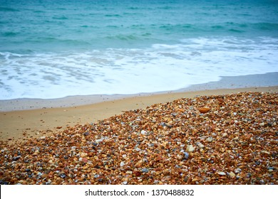 Bournemouth sandy beach with colourful pebble stones creating picturesque holiday seaside background. Calm turquoise sea waves create inner peace relaxing state of mind. Dorset UK