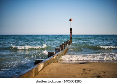 Bournemouth seafront with beautiful sandy beach and calm sea waves during summer day. Dorset Coast Holiday Background. Popular tourist destination in south west of England.
