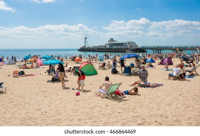 BOURNEMOUTH, UK - 09 AUGUST 2016: General view on the beach in Bournemouth with pier amusements in the background, in a sunny summer day.