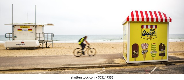 BOURNEMOUTH, UK - AUGUST 22, 2017: Cyclist Rides passed a Life Guard Station towards a Walls Ice Cream Stand on Bournemouth Beach
