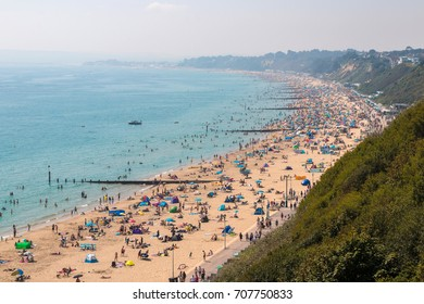 BOURNEMOUTH, UK - AUGUST 28, 2017: Busy beach in a hot summer day. View from the top of the cliffs