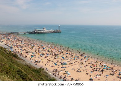 BOURNEMOUTH, UK - AUGUST 28, 2017: Busy beach in a hot summer day with Pier Amusements in the background. View from the top of the cliffs