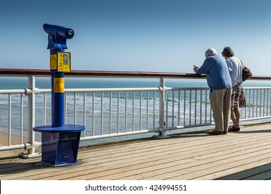 BOURNEMOUTH, UK - MARCH 9, 2014:  Elderly couple stand on the pier and look at the sea