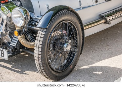 Bourton-on-the-Water, Gloucestershire UK 04/30/19 One of the front wheels and headlights of a Morgan S and S 3-Wheeler car, parked in car park on a dry sunny day. No people in image. Silver body.
