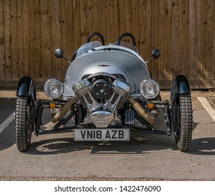 Bourton-on-the-Water, Gloucestershire UK 04/30/2019 Front view of a Morgan S and S 3-Wheeler motor car, parked in car park on a dry sunny day. No people in image. Silver body. Wooden fence in behind.