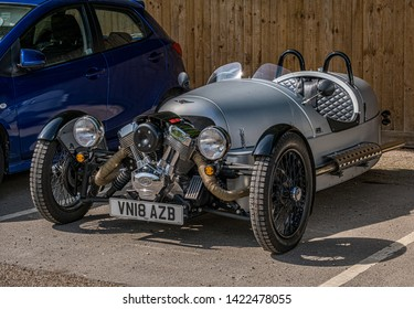 Bourton-on-the-Water, Gloucestershire UK 04/30/2019 Side view of a Morgan S and S 3-Wheeler car, parked near a blue car in car park on a dry sunny day. No people in image. Silver body.