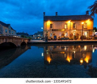 BOURTON-ON-THE-WATER/GLOUCESTERSHIRE/ENGLAND-8/28/2018:  Bourton-On-The-Water in rural Cotswolds england on a summers evening with reflections of light on the river Windrush.