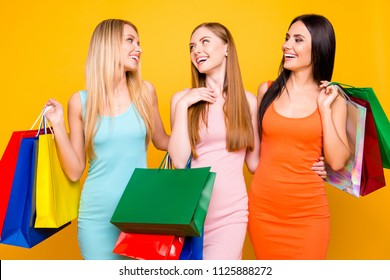 Boutique center mall package commerce black friday concept. Portrait of funky positive trio going from showroom having many colorful bags sharing funny news isolated on bright yellow background