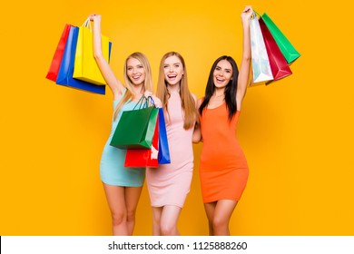 Boutique center mall showroom package commerce black friday concept. Portrait of cheerful fancy trio holding colorful bags in raised hands enjoying seasonal sales isolated on bright yellow background