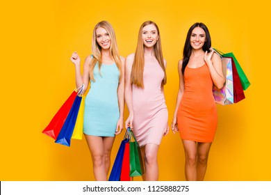 Boutique mall showroom package commerce rest relax leisure black friday concept. Portrait of slim trio going from shopping center holding a lot of bags in hands isolated on vivid yellow background