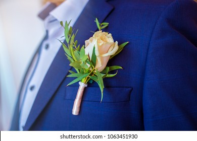 Boutonniere in form of rose on wedding suit of groom