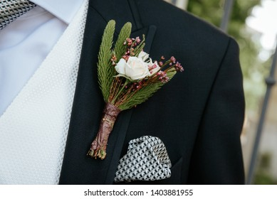 Boutonniere with a rose and sprig of fir on the background of the groom's jacket.