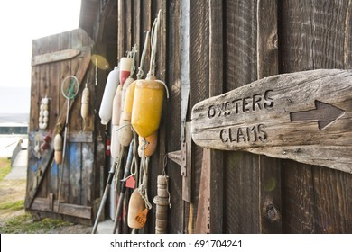 Bouys and a sign for oysters and clams hang on a shed at a shellfish farm on Orcas Island, Washington.