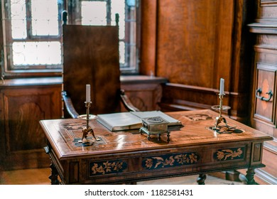 BOUZOV, CZECH REPUBLIC - AUGUST 8, 2018: Picture of the medieval desk with a book and candlesticks.