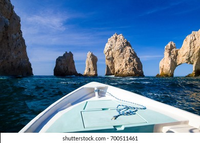 Bow of boat approaching large rock formation on the ocean in Cabo San Lucas, Mexico