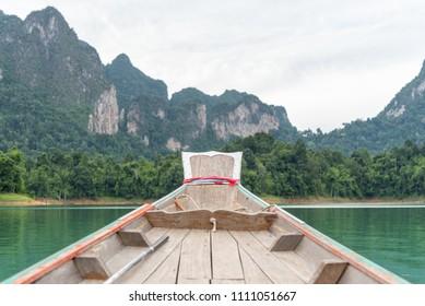 Bow of boat heading forward on emerald lake. Ratchaprapha Dam at Khao Sok National Park.