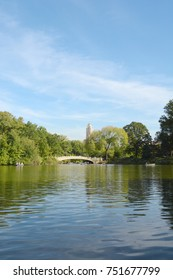 Bow Bridge crosses The Lake in Central Park, Manhattan, New York. The calm water reflects the surrounding green trees.