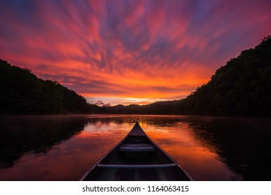 Bow of canoe and dramatic sunset