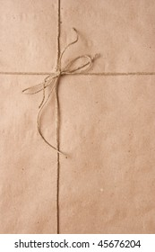 Bow from a cord on a brown packing paper