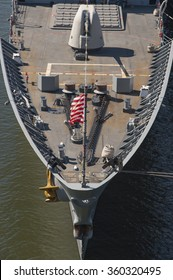 The bow of a grey US warship sailing in the sea