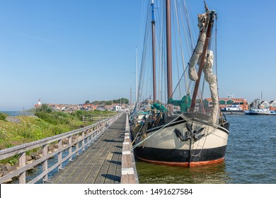 Bow of historic sailing ship moored at pier of Dutch fishing village Urk