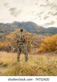 bow hunter man dressed in camouflage in the mountains at sunrise