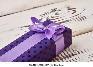 Bow on purple gift box. Present package on wooden plank. Aesthetic way of greeting.