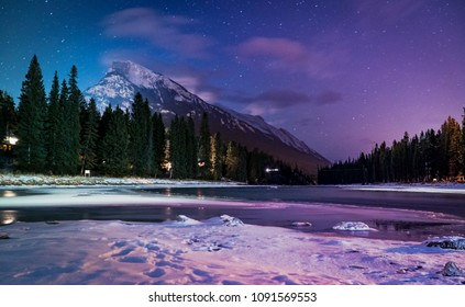 Bow River and Mt Rundle in Banff, Alberta under a clear starry sky.