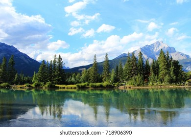 Bow river view from the Banff village, beautiful typical Canadian nature - mountains with the tree's reflection in the clear cyan water