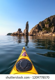 The bow of the sea kayak on the background of the rocky sea coast.
