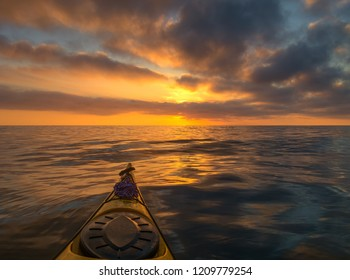 The bow of the sea kayak on the background of a beautiful sea sunset.