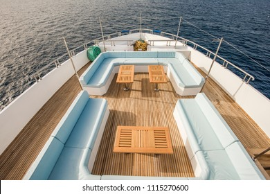 Bow teak deck of a large luxury motor yacht with chairs sofa table and tropical sea view background