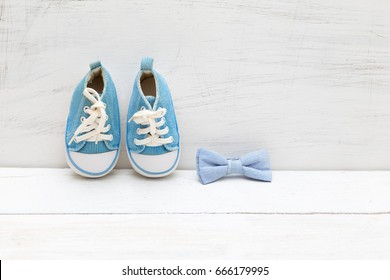 bow tie and children's blue sneakers on a white wooden background