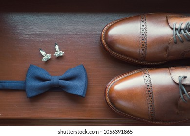 Bow tie, cuff links and men's shoes close-up.