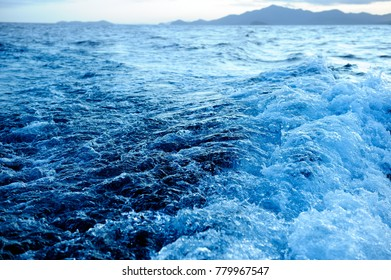 Bow wake created by recreational boat moving through blue ocean in evening light.