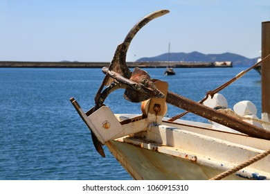 The bow of a white boat with a rusted metal anchor in the seaport.