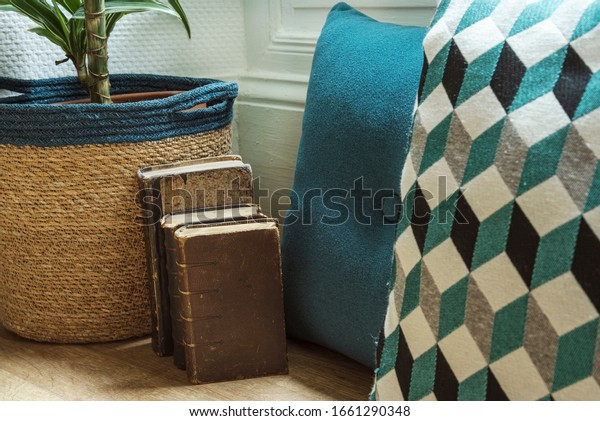 Bow window decoration with plant, turquoise cushions and old books posed on wooden floor.