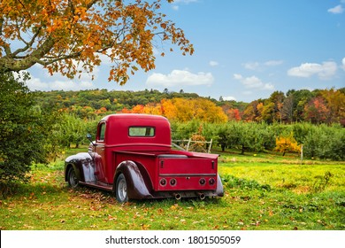 Bowdoin, Maine - October 12, 2018: Old antique red farm truck in apple orchard against autumn landscape background. Blue sky on a sunny fall day in New England.