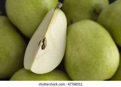 A bowel full of Pears with one cut quarter