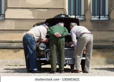 Bowes / Great Britain - May 8, 2016: Three old men inspect the engine under the bonnet of a Morris Minor Classic Car