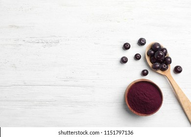 Bowl of acai powder and fresh berries on light wooden table, flat lay with space for text
