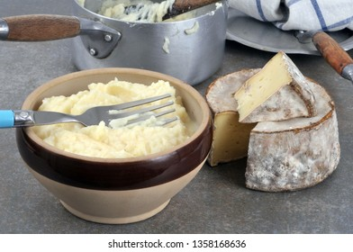 Bowl of aligot with a piece of cheese