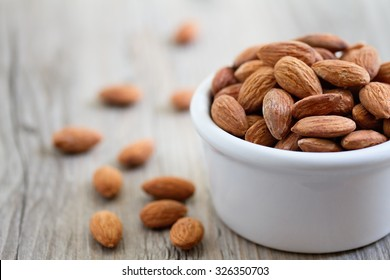 Bowl of almond nuts on rustic wooden table in natural light.
