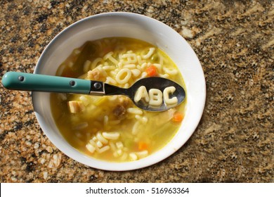 bowl of alphabet soup on counter with abc spelled out on spoon