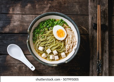 Bowl of asian style soup with green tea soba noodles, egg, mushrooms, spring onion and tofu cheese, served with chopsticks and white spoon over old wooden background. Top view, copy space