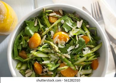A bowl of asparagus salad with orange slices, almond slices, and orange vinaigrette