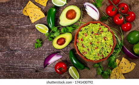 Bowl of Avocado Guacamole Mexican Dip with Avocado, Lime, Tomato, Cilantro with Fresh Ingredients with Tortilla Chips. Selective focus.