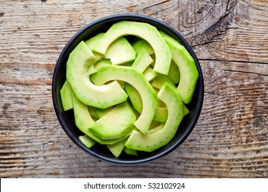 Bowl of avocado slices on wooden background, top view