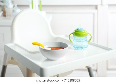 Bowl with baby food on highchair indoors